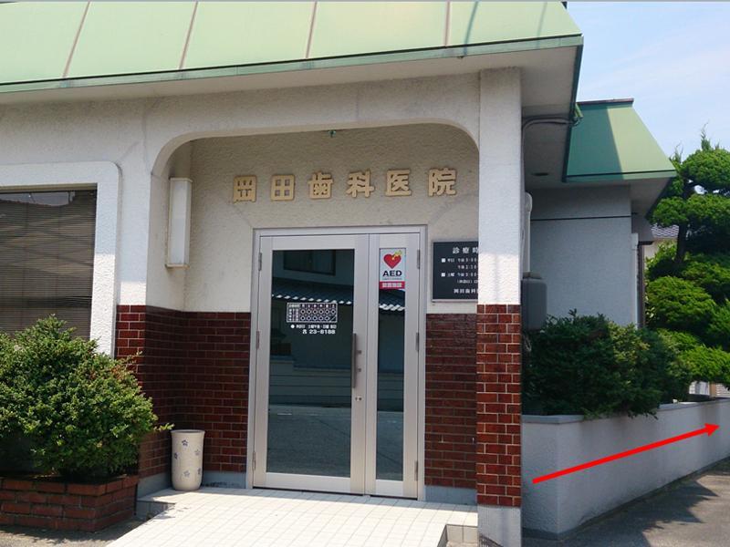 正面玄関(駐車場へは矢印の方向へ)